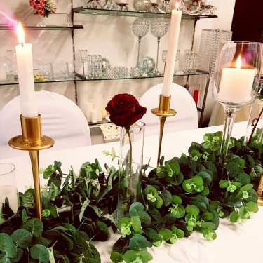Gold candlesticks and foliage centrepiece