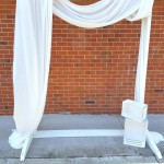 white wooden wedding arch